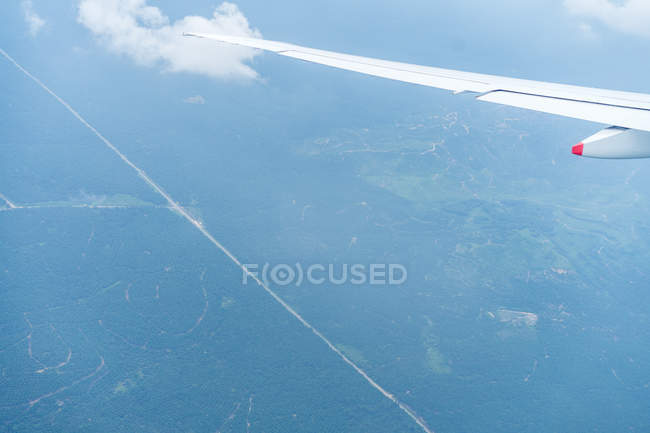 Aerial view green landand big wing of airplane. — Stock Photo