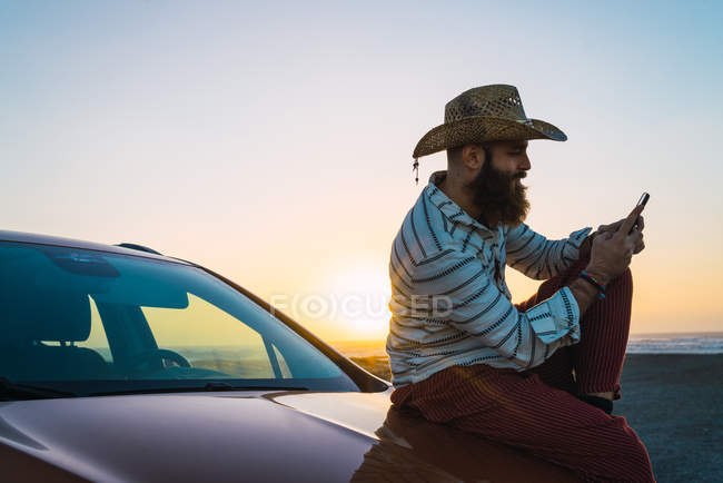 Side view of bearded traveler sitting on car and browsing smartphone — Stock Photo
