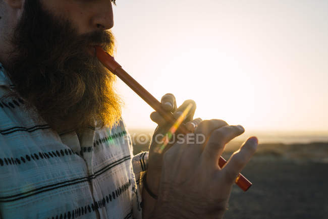 Ernte-Schuss bärtigen Mannes spielen Rohr auf Grund der sonnigen Küste. — Stockfoto