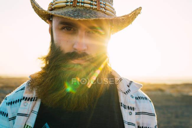 Retrato de hombre barbudo en sombrero contra la luz del sol - foto de stock