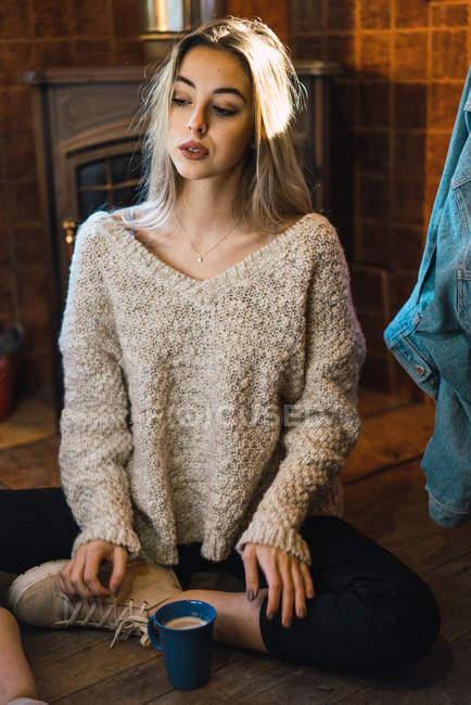 Молодая чувственная модель в свитере с чашкой кофе, позируя на полу дома и глядя в сторону . — стоковое фото