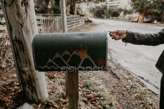 Crop person opening mailbox on roadside — Stock Photo