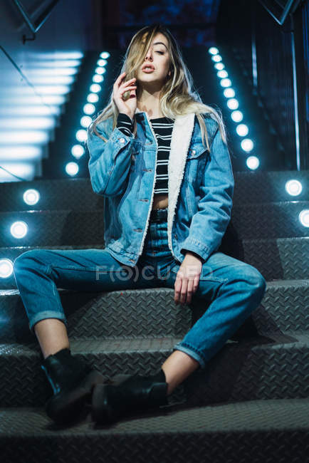 Portrait of provocative blonde girl sitting on steps and looking at camera — Stock Photo