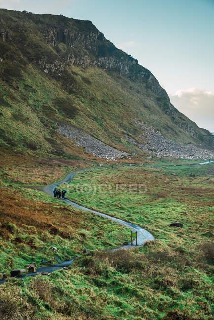 Vue lointaine du groupe de touristes debout sur la route dans les montagnes — Photo de stock