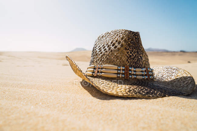 Close up view of cowboy straw hat on sand — Stock Photo