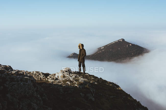 Man on rocky cliff against mountain peak looking out of clouds — Stock Photo