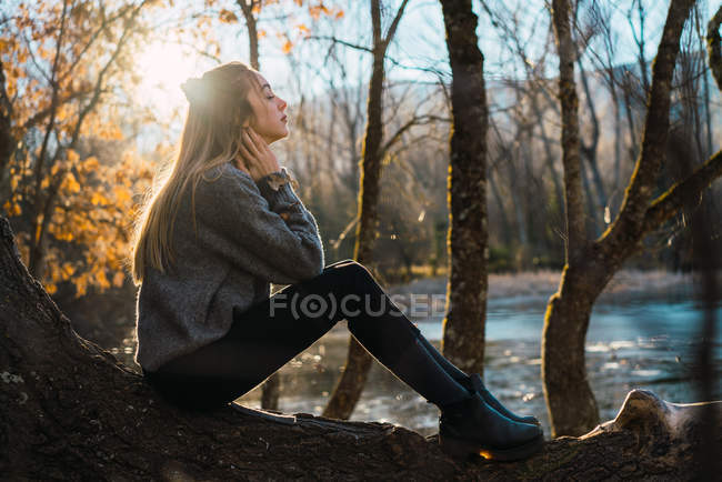 Vista lateral da mulher posando no tronco com os olhos fechados no fundo do rio na floresta outonal . — Fotografia de Stock
