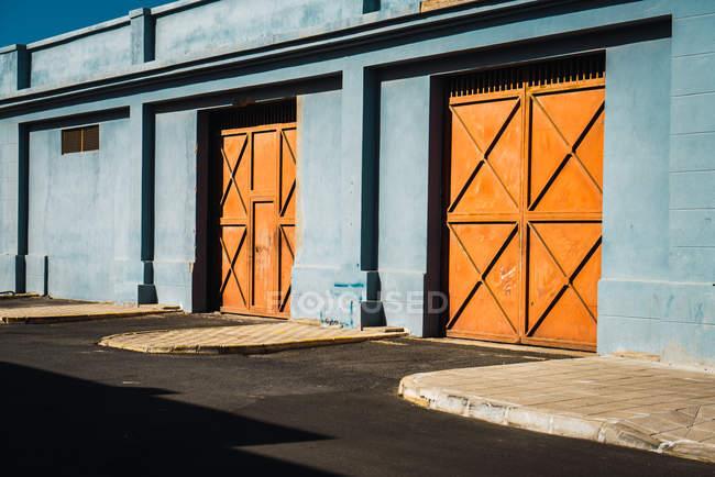 Vista exterior de portões laranja na parede azul — Fotografia de Stock