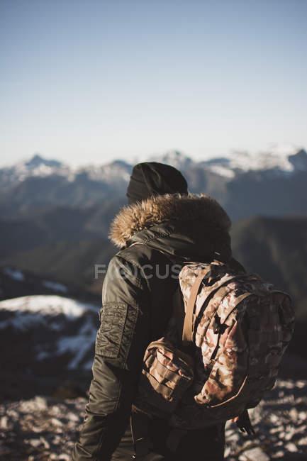 Vista traseira do homem com a mochila olhando montanhas nevadas — Fotografia de Stock