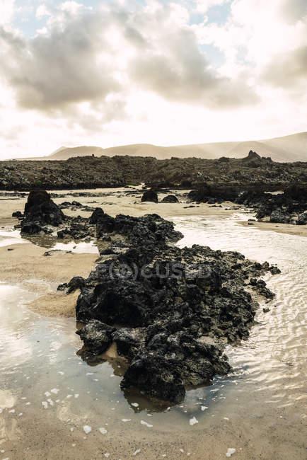 Close-up vista de pedras vulcânicas, em meio a vala de água — Fotografia de Stock