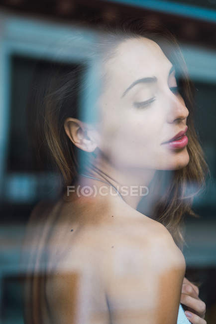 View through window of sensual woman with eyes closed — Stock Photo