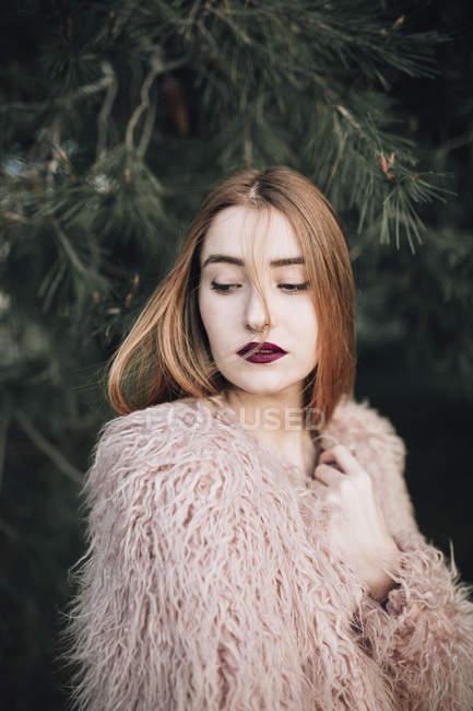 Ragazza sensuale in pelliccia accogliente guardando lontano sullo sfondo di abete — Foto stock