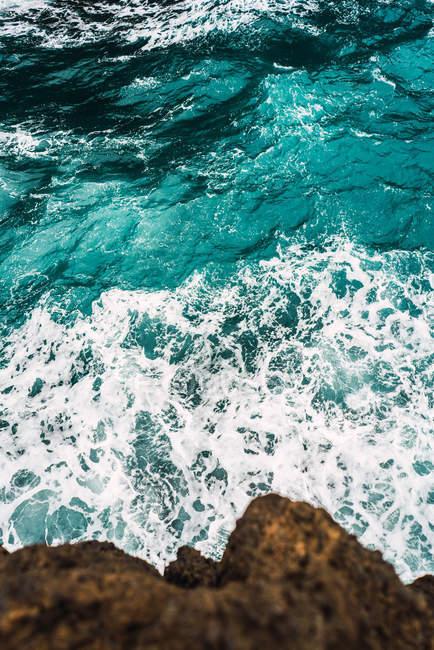Сверху вид прибрежных скал и бирюзовый океан волнистые — стоковое фото