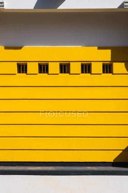 Vista exterior del edificio moderno con fachada de amarillo y filas de windows - foto de stock