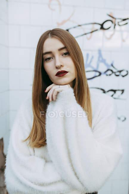 Ragazza sognante in posa bianca su sfondo di muro grungy e guardando la fotocamera — Foto stock