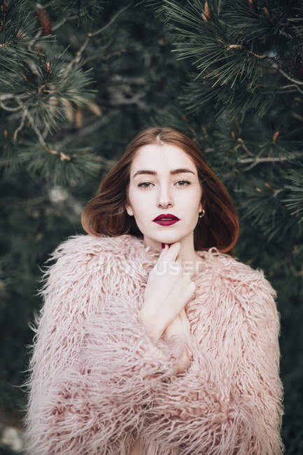 Sensual young girl with bright lips posing by fir branches and looking at camera — Stock Photo