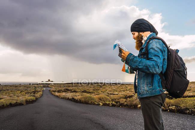 Vista laterale dell'uomo barbuto turistiche in piedi sulla strada rurale e guardando mappa mappa nelle mani — Foto stock