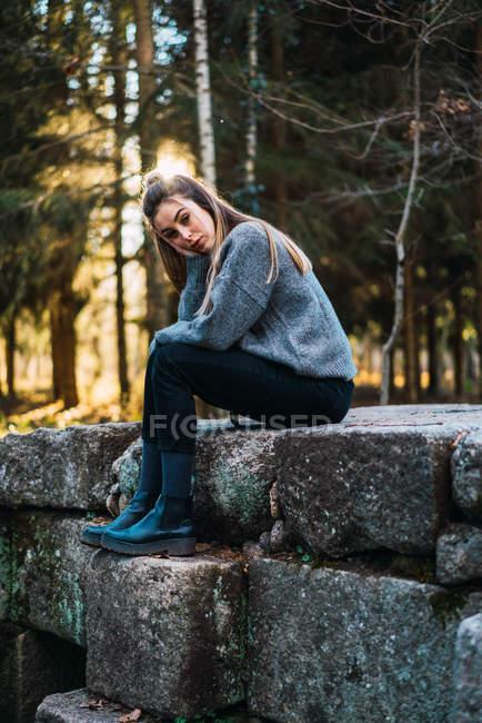 Портрет молодої жінки, спираючись з боку і, сидячи на кам'яній стіні у осінній ліс — стокове фото