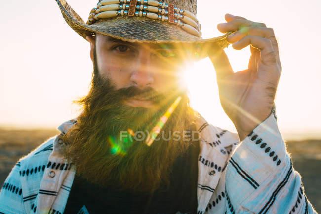 Retrato del hombre barbudo posando en sombrero contra la luz solar - foto de stock
