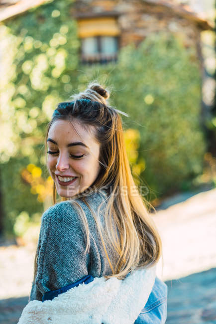 Portrait of young woman in sweater posing flirty with eyes closed on urban street. — Stock Photo