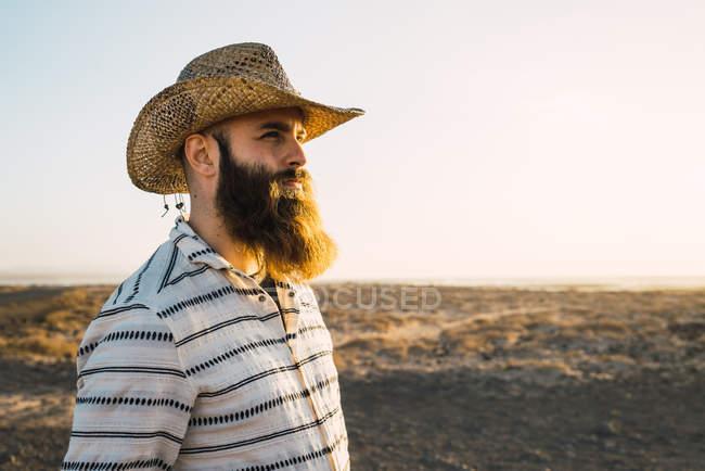Vista lateral del hombre barbudo en sombrero de paja vaquero contra la luz solar - foto de stock