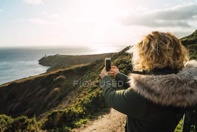 Резервного зору туристичних жінка, стоячи на прибережні скелі і приймають знімки моря з смартфон — стокове фото