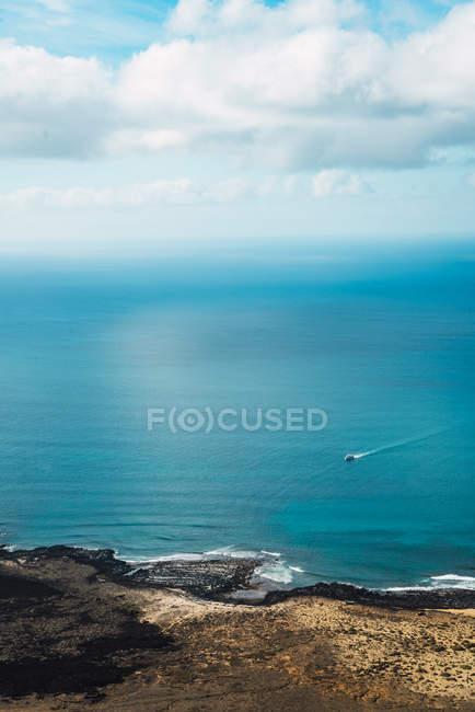 Отдаленное представление о небольшой лодке в синем море — стоковое фото