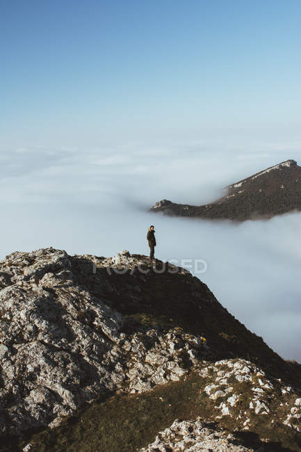 Distant view of man on rocky cliff in clouds — Stock Photo