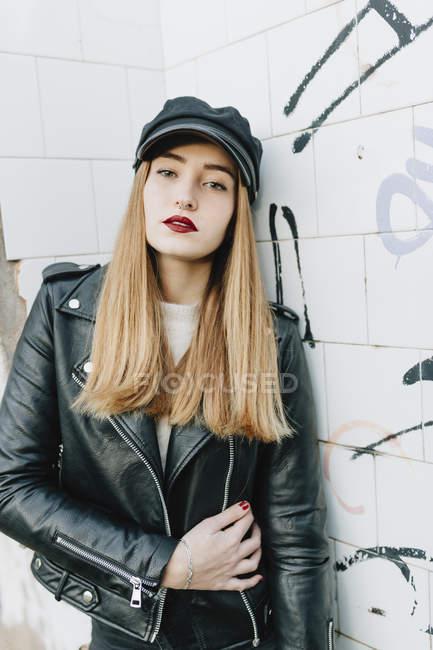 Stylish model in black on grungy background — Stock Photo