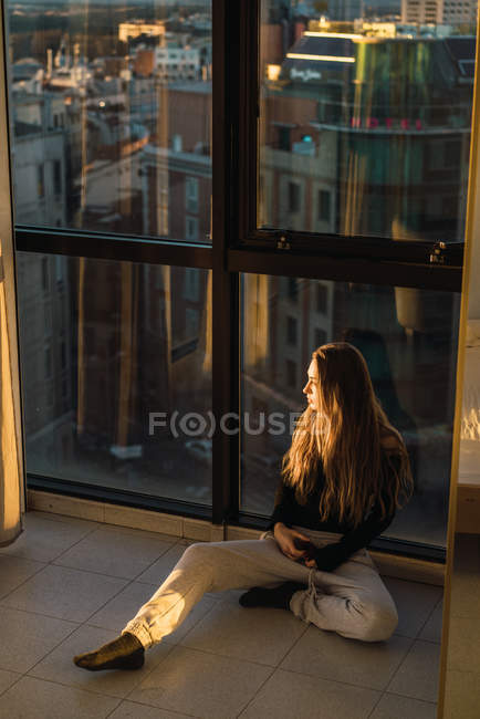 Blonde woman sitting in floor near window and looking away — Stock Photo