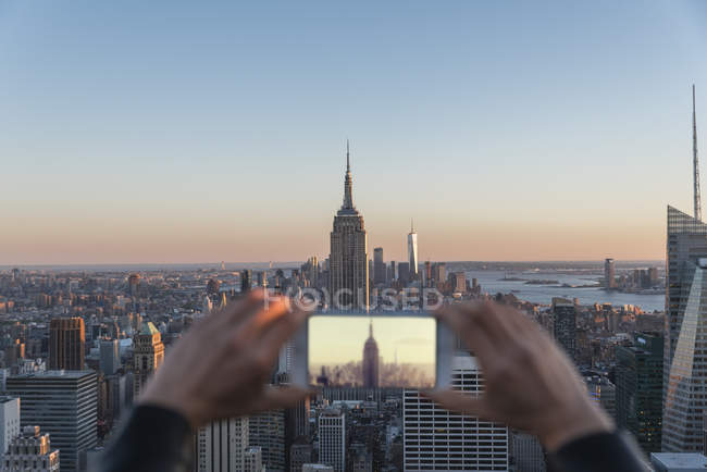 Crop female hands taking picture of New York skyline with smartphone — Stock Photo
