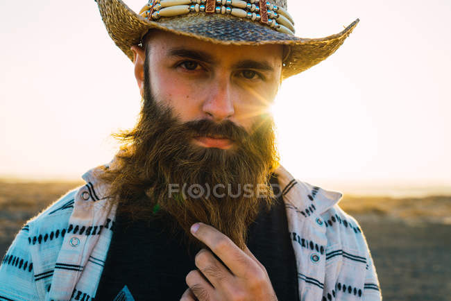 Portrait of bearded man in hat palming beard and looking at camera — Stock Photo