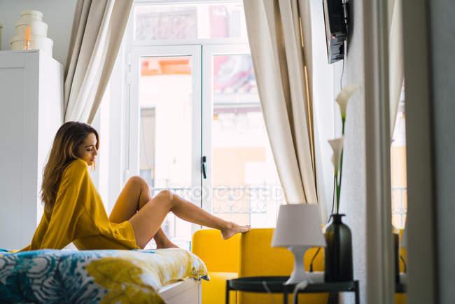 Вид збоку чарівною жінці, лежачи на ліжку у себе вдома — стокове фото