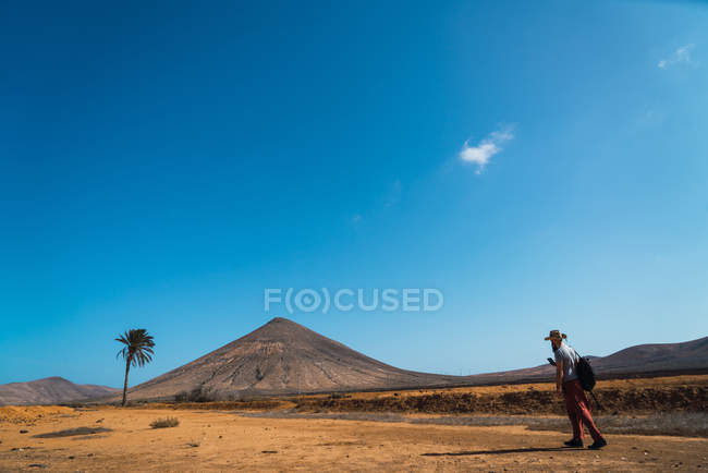 Side view of traveler with backpack walking on dry sandy terrain with mountains on background. — Stock Photo