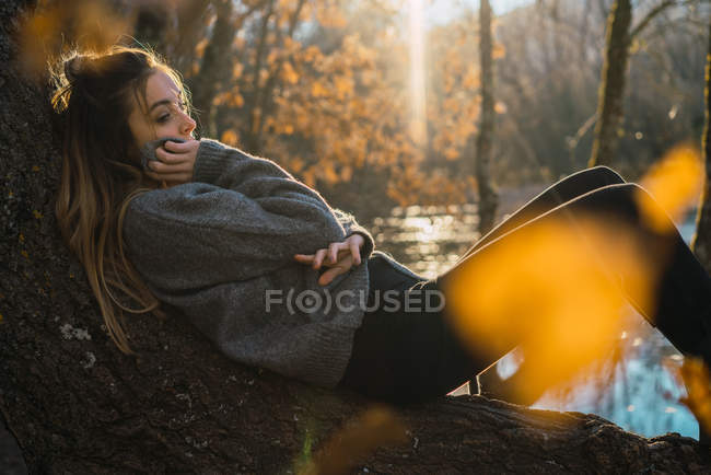 Вид сбоку мечтательной женщины, лежащей на багажнике в осенних нарядах — стоковое фото