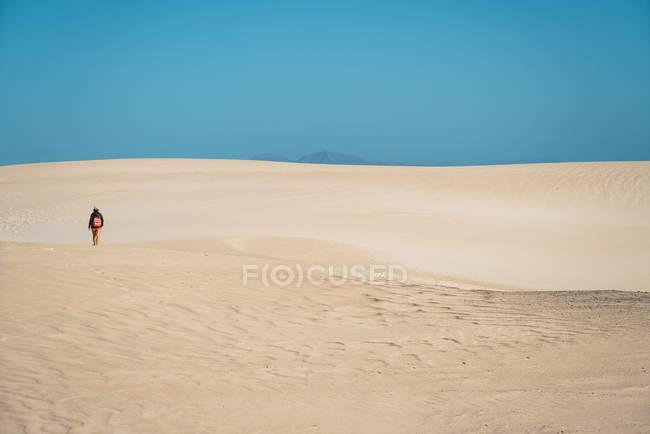 Vue arrière du voyageur avec sac à dos, marcher dans les dunes de sable — Photo de stock