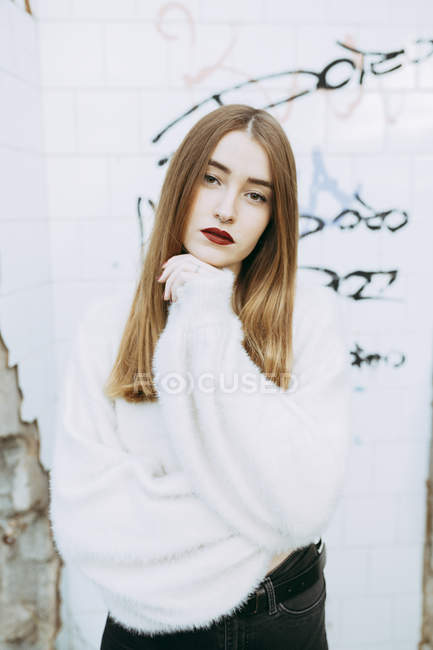 Retrato de menina sonhadora em suéter branco posando no fundo da parede grungy — Fotografia de Stock