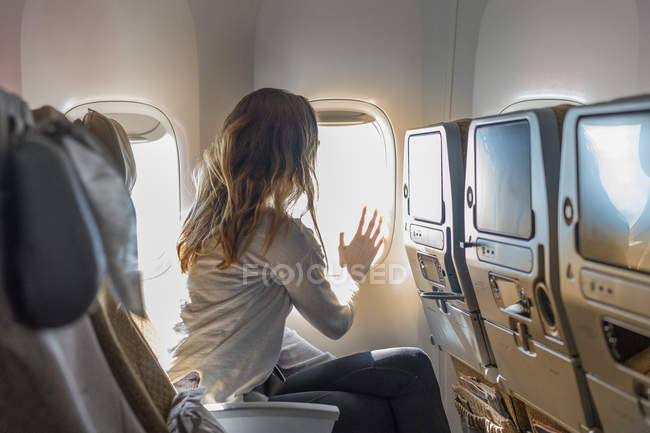 Side view of unrecognizable tourist touching window in airplane. — Stock Photo