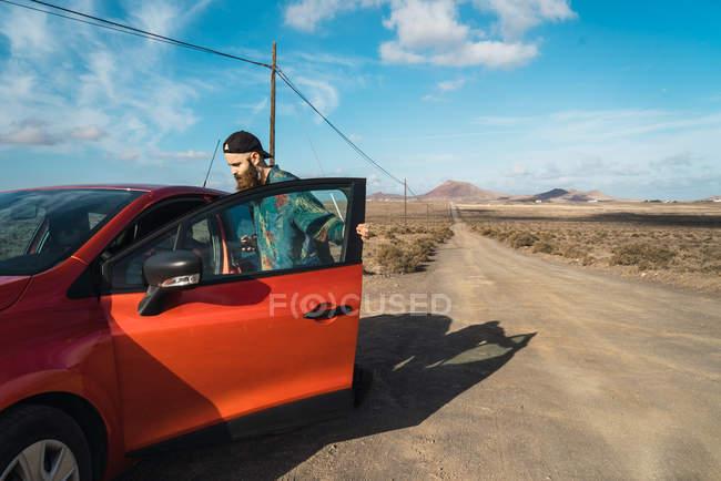 Вид збоку бородатий туристичних попадання в червоний автомобіль на сільській дорозі — стокове фото