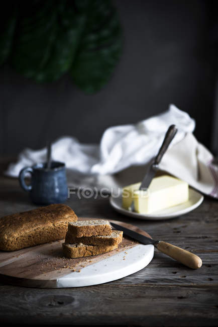 Still life of homemade cake slices on board and butter at wooden table — Stock Photo