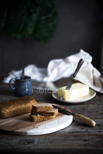 Stillleben mit hausgemachte Tortenstücke an Bord und Butter an Holztisch — Stockfoto