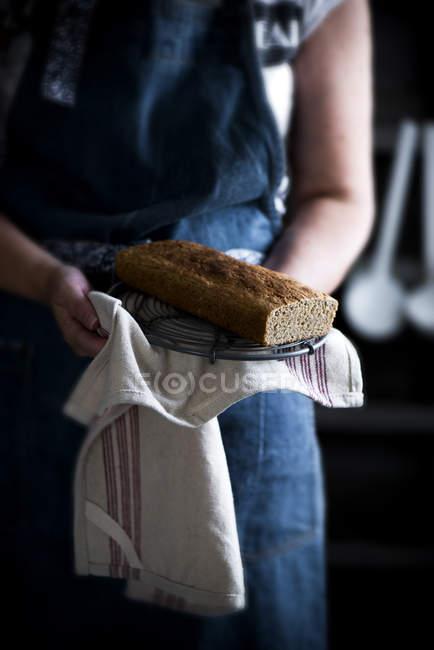Mittelteil der weiblichen Holding hausgemachten Kuchen auf Handtuch in Händen — Stockfoto