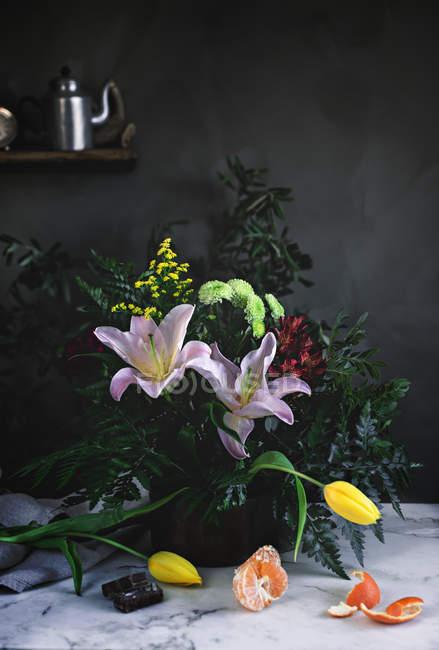 Stillleben mit Blumen Blumenstrauß auf Tisch mit Mandarine — Stockfoto