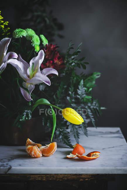Stillleben mit Blumen Blumenstrauß auf Tisch mit Mandarinen Stücke — Stockfoto