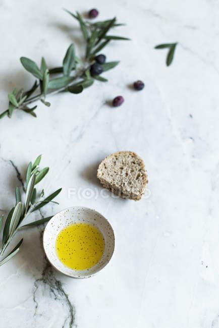 Directamente desde arriba vista de aceite de oliva en el tazón y ramas de olivo con pan sobre fondo blanco - foto de stock