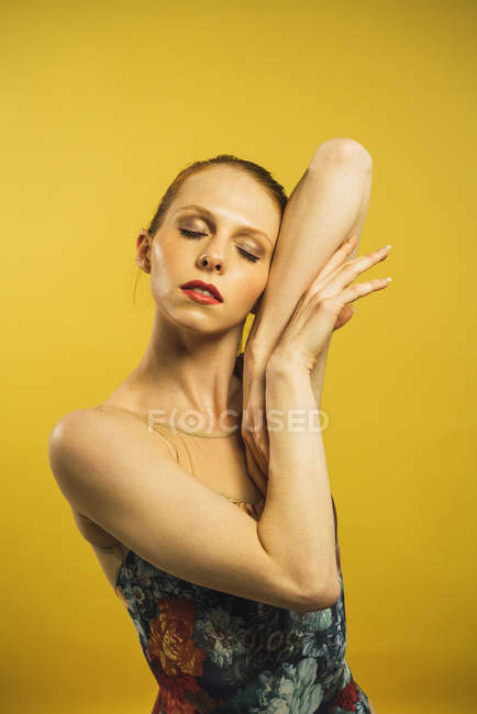 Portrait of redheaded woman standing with eyes closed and posing on yellow background. — Stock Photo