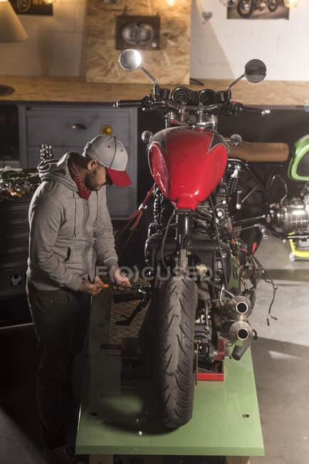 Professional mechanic fixing custom motorbike at workshop — Stock Photo