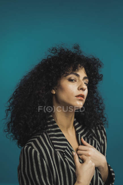 Curly woman in striped jacket posing on blue background — Stock Photo