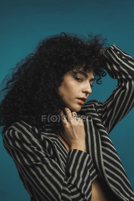 Curly woman in striped jacket posing in studio — Stock Photo