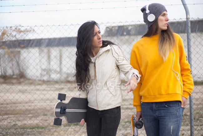 Портрет двух девочек с longboard, глядя в сторону на уличная сцена — стоковое фото